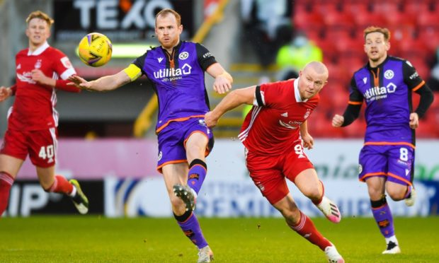 Dundee United captain Mark Reynolds and Aberdeen's Curtis Main in action.