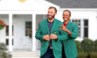 Last year's Masters champion Tiger Woods, right, presents Dustin Johnson with his first green jacket after winning the Masters golf tournament Sunday, Nov. 15, 2020, in Augusta, Ga. (Curtis Compton/Atlanta Journal-Constitution via AP)