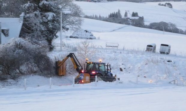 A council tractor cutting back bushes at the side of the untreated road in Belnagarrow, Craigellachie. More than four inches of snow had fallen.