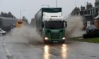 A lorry splashes through floodwater on the A90 at Boddam. Picture by Kenny Elrick