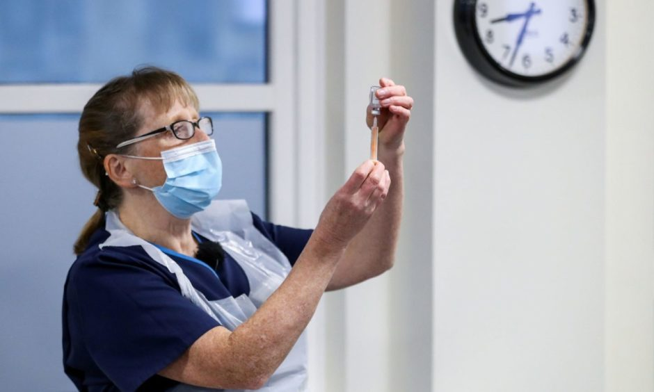 A healthcare worker holds a vial of the Oxford/AstraZeneca coronavirus vaccine at Pentlands Medical Centre in Edinburgh.