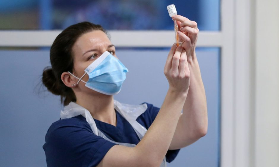 A healthcare worker fills a syringe with a dose of the Oxford/ AstraZeneca coronavirus vaccine in Edinburgh, Scotland, as the government continues to ramp up the vaccination programme.
