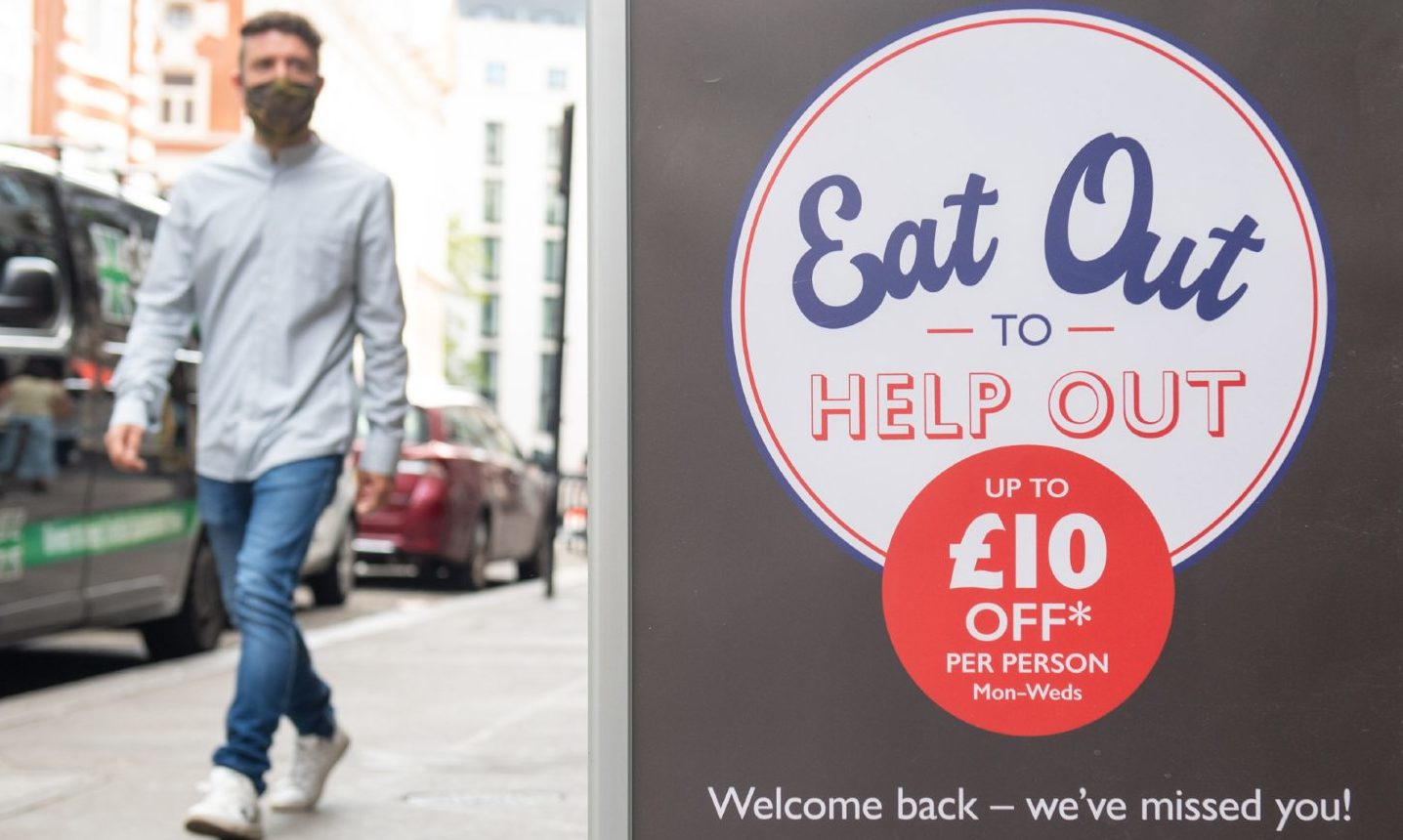 A man walks past an Eat Out To Help Out sign.