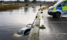 Police at the scene where the car went into the river in Nairn.