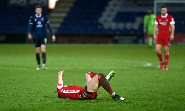 Aberdeen's Ross McCrorie lies injured on the Global Energy Stadium pitch. Picture by Darrell Benns