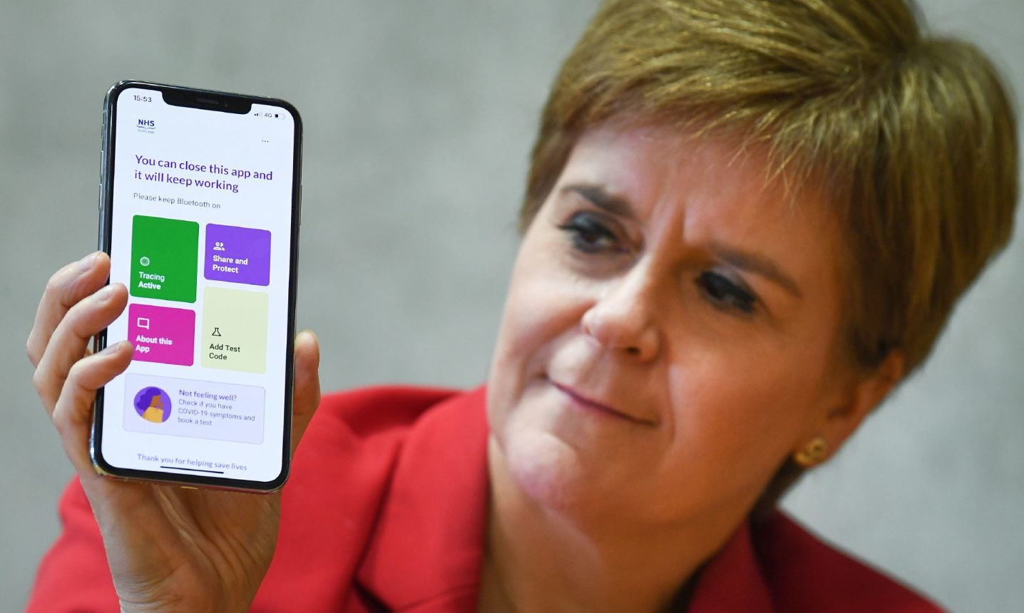 First Minister Nicola Sturgeon views the new Covid-19 track and trace app on a phone at the Scottish Parliament.