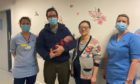 Kieran and Kun Gullett and baby  January 1, 2021 with NHS staff at Aberdeen Maternity Hospital.