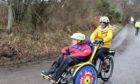 Angelman James Murray from Kirkhill on his new electric duet bike, pedalled by his mum Kathleen