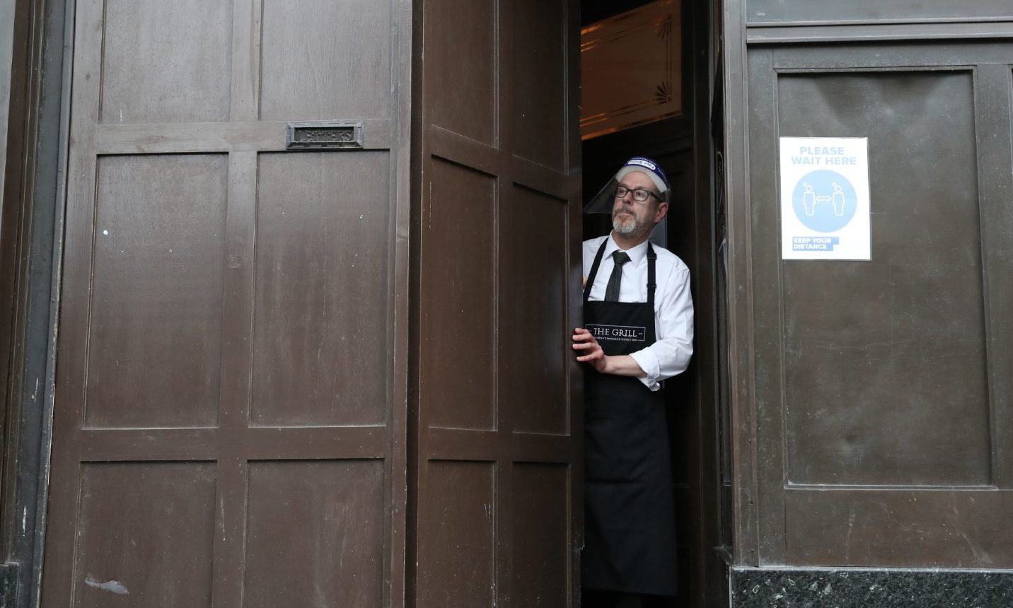 Keith McKenzie closes the door of The Grill in Aberdeen as lockdown restrictions are imposed.