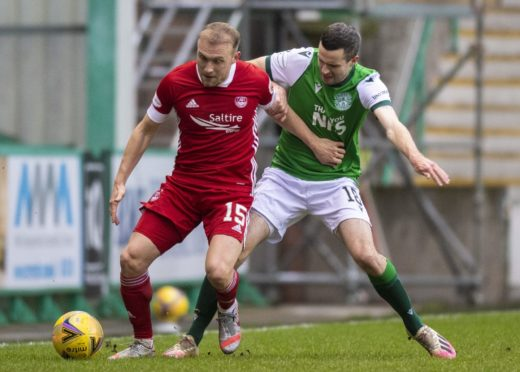 Dylan McGeouch holds off Jamie Murphy of Hibs.