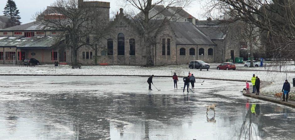 People skating at Cooper Park's pond in Elgin.