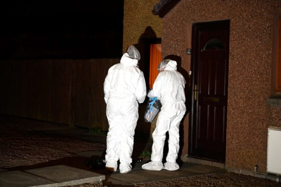 Forensic officers examined the scene after the woman was found. Picture: Kenny Elrick