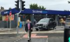 MSP David Stewart pictured using the newly installed puffin crossing on the A82 on Glenurquhart Road at Smith Avenue.