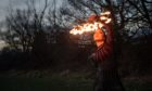 """Fire performer Dawn Bryant practices at a park near her home in Birmingham. Picture date: Thursday February 11, 2021. PA Photo. The fire performer has been forced to """"completely 360"""" and take work as a carer due to the Covid-19 pandemic. Dawn Bryant used to do a large number of international choreographed shows including fire breathing, pyrotechnics and fire spinning, accompanied by music. See PA story HEALTH Coronavirus Careers. Photo credit should read: Jacob King/PA Wire"""