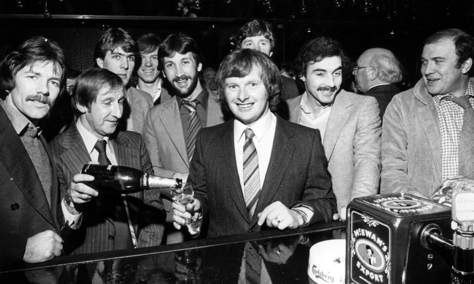 Former Dons manager Ally MacLeod pours a glass of champagne for Aberdeen's sharpshooter Joe Harper at the opening of Joe Harper's Lounge, Union Street, in 1980 while other members of the Dons team look on.