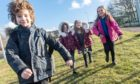 Children from Smithton Primary School near Inverness are pictured leaving school after their first day back after the most recent lockdown. Pictured are Ewen Robertson P3, Twins Amelia and Isla P2 and Anna Munro P3 Pictures by JASON HEDGES