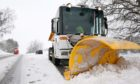A gritter clears snow.
