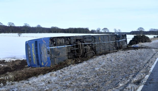 The Megabus lying on its side off the A90. Picture by Chris Sumner