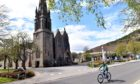 A cyclist passes Glenmuick Church in Ballater, where a planning application to 'transform' the village has been lodged.