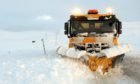 A snow plough at work in the Highlands