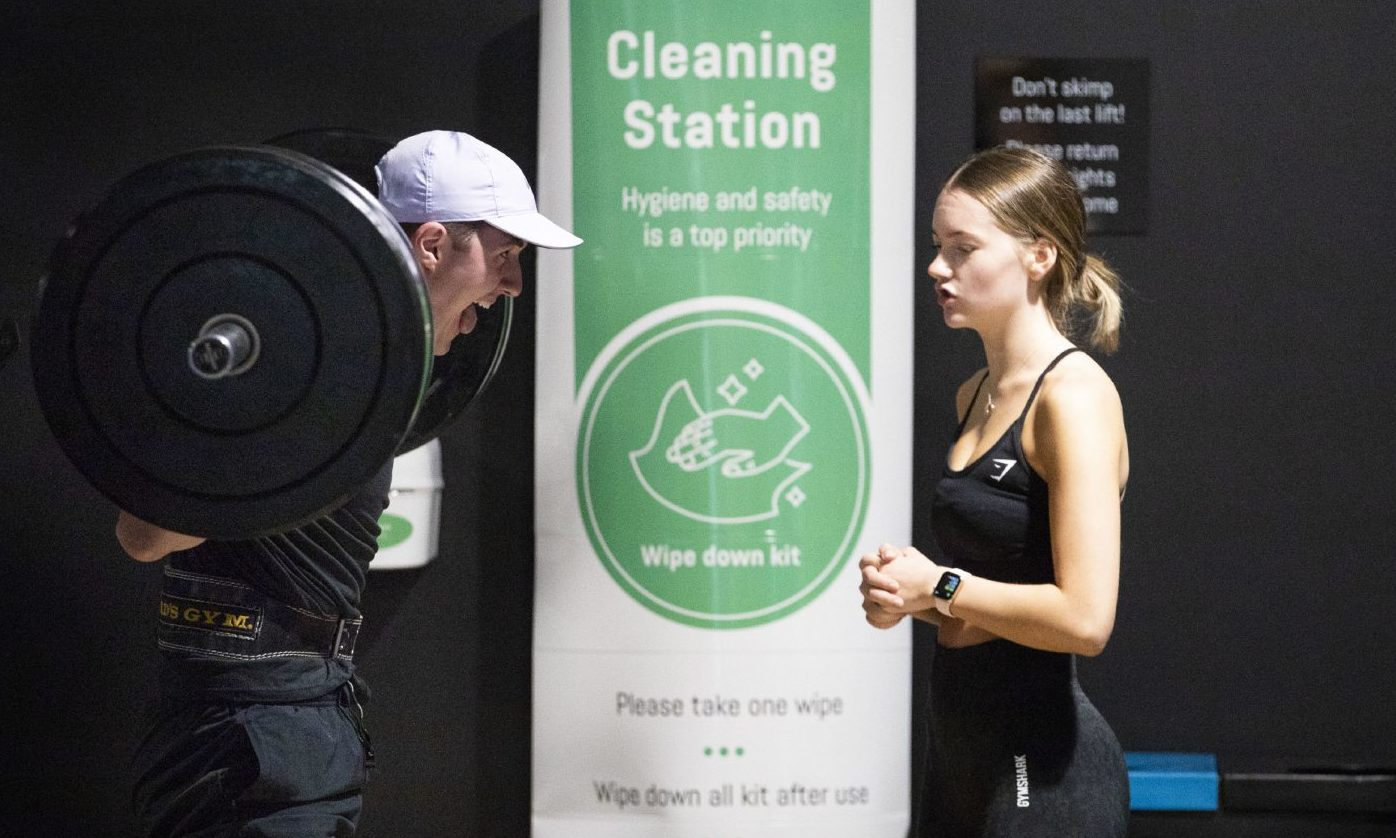 Gym members work out beside a PureGym cleaning station.