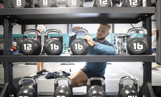 Gym member Brydon Smith cleans the weights after a workout at the new PureGym Local in Kirkcaldy, Fife.