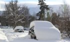 Snow-covered cars parked on the street in Braemar.