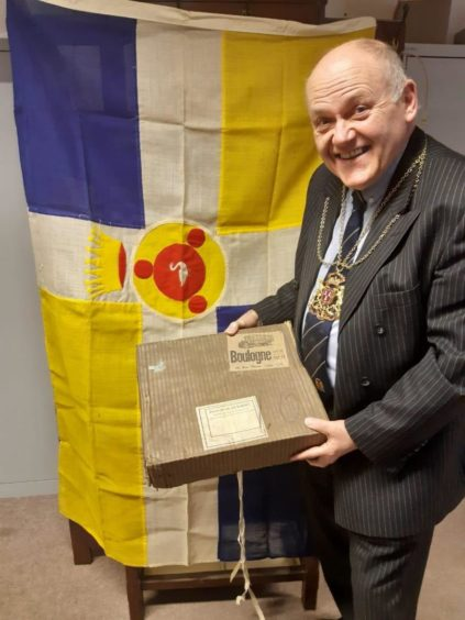 Lord Provost Barney Crockett in front of the Boulogne-sur-mer flag sent to Aberdeen in friendship in 1934, after the Gordon Highlanders fought in the area during the First World War.