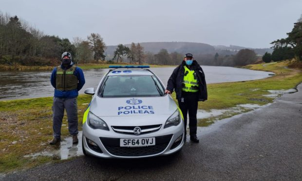 A Dee District Salmon Fishery Board fisheries officer, alongside a Police Scotland officer, at the banks of the River Dee.