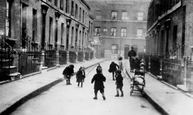 Children playing outside their slum dwellings in Laursa Place, Shoreditch, London, c.1920.
