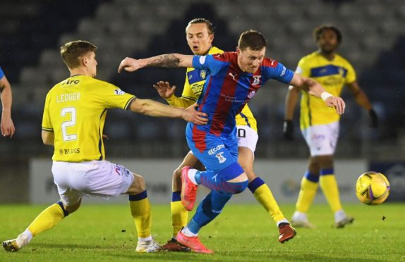 Shane Sutherland of Inverness (centre) looks to break free from Michael Ledger (L) and Aidan Nesbitt of Morton.
