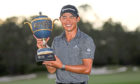 Collin Morikawa of the US celebrates with the championship trophy after winning the World Golf Championships - Workday Championship at The Concession golf tournament in Bradenton, Florida.