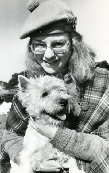 Ulrike Lorenz (17) from Stuttgart makes friends with West Highland terrier Pipey at the 1980 Games.