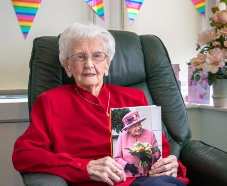 Mrs Robertson with her card from the Queen