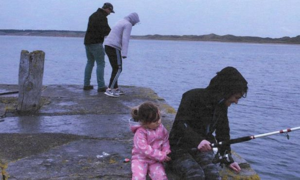"""Muriel Murray showing her family fishing """"completely unsuccessfully"""" in the rain at Castlehill harbour."""
