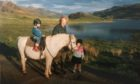 Katie Scobie on the horse, with her late father Ewen and sister Kim.