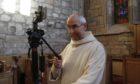 Brother Michael de Klerk sets up one of the cameras for livestreaming.