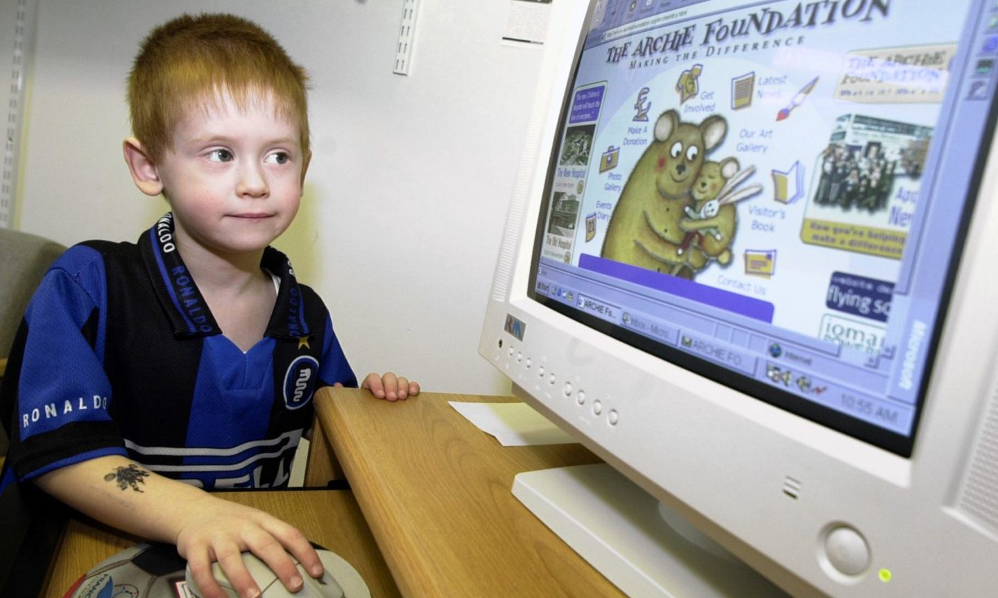 Four-year-old Calum Brunning logs on to the new Archie Foundation website in 2001.