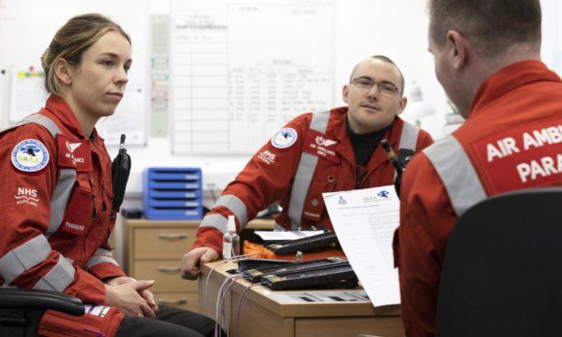 Scaa paramedics Laura McAllister, Ewan Littlejohn and Rich Forte discuss a brief at the charity's Aberdeen airport base
