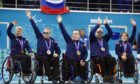 From left, Great Britain's Angie Malone, Jim Gault, Bob McPherson, Gregor Ewan, and Aileen Neilson celebrate after wining bronze medals after the wheelchair curling match between Great Britain and China at the 2014 Winter Paralympics in Sochi, Russia.