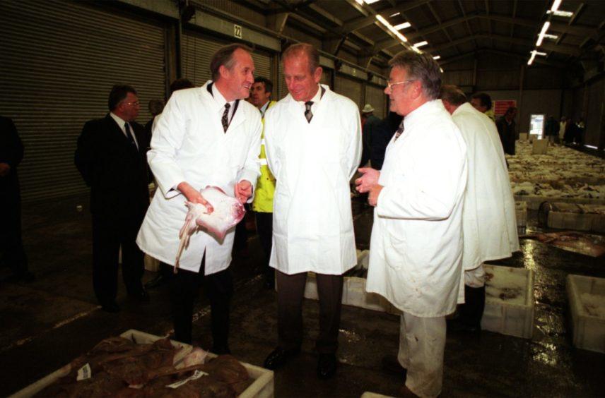 Robert Milne (left) M.D Aberdeen Fish Curers Merchant Asso, shows Prince Philip around Aberdeen's fish market, along with Jim Gordon Chairman of Aberdeen Fish Salesmen's Association (right)