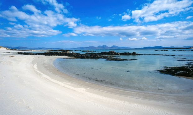 Empty white sandy beach near the Strand on the Hebridean Island of Colonsay in Summer with the Island and Paps of Jura on the horizon.
