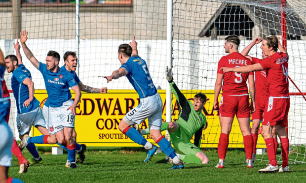 Stranraer celebrate scoring at Dudgeon Park as the Brora players watch on.