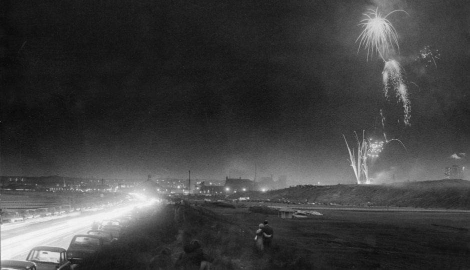 """26.06.1972. Sparkling festival fireworks illuminate the Broad Hill and bring Aberdeen Festival to a spectacular and colourful close on Saturday. This picture was taken by staff photographer Jim Love using a fast panchromatic film. With cars and their glaring headlights passing him on the promenade during this three minute """"take"""" he had to shield his camera lens."""
