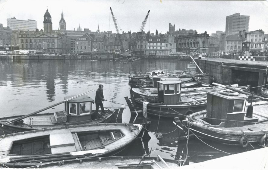 """1974-03-27 D  """"The fleet of small boats at Aberdeen has a temporary home. The traditional base for the vessels has been Torry Harbour at the mouth of the Dee, but the harbour - considered to be the original home of the local fishing industry - is being filled in for an oil company development. In the meantime the small boats, used for fishing and pleasure, have been moved to the Upper Dock. Danny Ross, one of the small boat owners, ties up his vessel, Roend at the south-east corner of the dock. The small boat owners recently formed an association and are considering a suggestion by Aberdeen Harbour Board that a new harbour should be built for the small boats further up the Dee."""" Picture taken by Jim Love"""