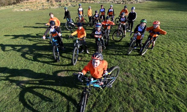 Pictured is Rory Nicholson, 7, with members of the Grampain Tigers Youth Cycling club behind him.