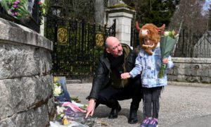 Flower tributes left at the Balmoral Castle front gate in memory of the late Duke of Edinburgh, Prince Philip. Pictured are Steve Mitchell and daughter Constance, 4.