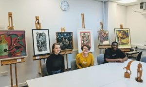 Dr Kate Cowcher (centre) and St Andrews alumni and project research assistants, Meredith Loper and Elikem Logan, with modern African artworks at Lochgilphead High School, March 2019.
