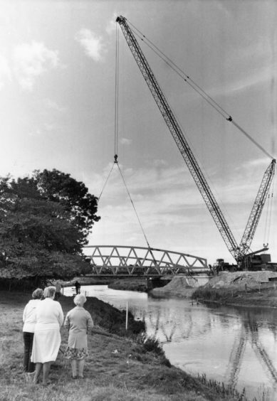 """19.09.1986 """"The positioning of Kintore's new bridge yesterday attracted a lot of attention and gave photographer Jim Love some good studies. The huge crane lowers the second steel truss into place."""""""