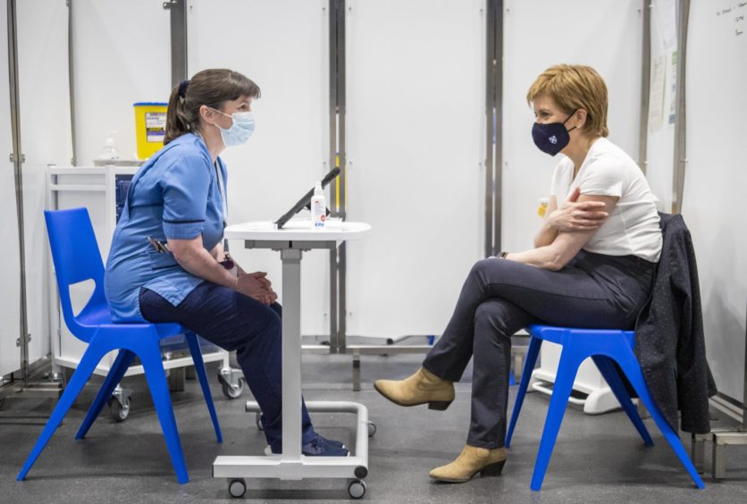 First Minister of Scotland Nicola Sturgeon (right) after receiving the first shot of the Astra Zeneca vaccine, administered by staff nurse Elaine Anderson, at the NHS Louisa Jordan vaccine centre in the SSE Hydro in Glasgow, Scotland. Picture date: Thursday April 15, 2021.